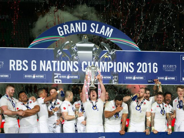 Rugby Union - 2016 Six Nations Championship - France vs. England England captain Dylan Hartley holds aloft the Six Nations trophy as his teammates spray champagne in celebration after winning the grand slam at The Stade de France, Paris. FOTOSPORT/WINSTON BYNORTH